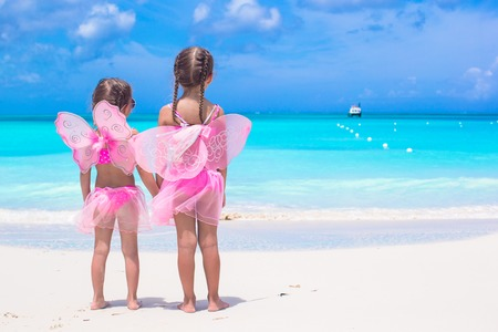 Adorable little girls with butterfly wings like butterfly on beach tropical vacation Stock Photo