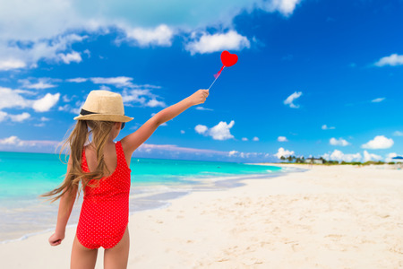 Little girl with red heart in hands on summer tropical beach photo