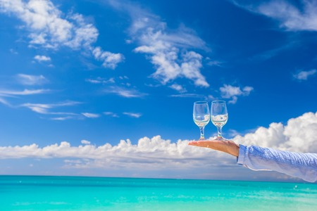 Two glasses on male hand on blue sky background photo