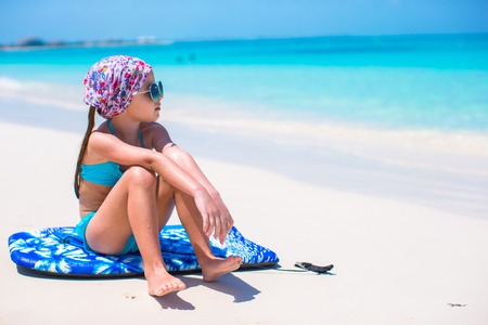 Adorable little girl sitting on surfboard at tropical white beach photo