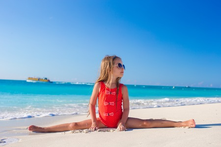 twine: Little girl sitting on the splits at the white beach