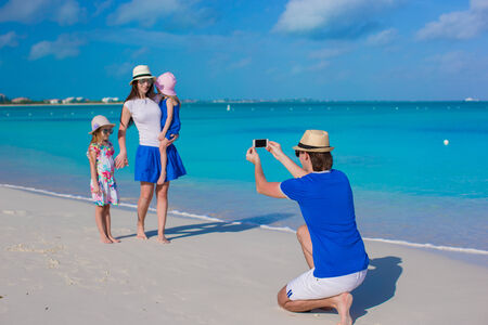 Young father making photo on phone of family at tropical beach photo