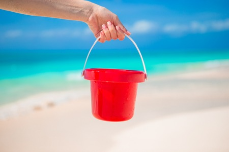 Close up hand holding a small red bucket on beach photo
