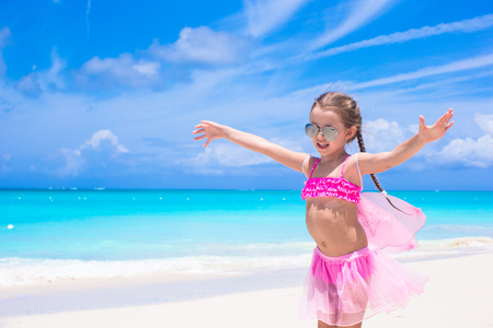 Adorable little girl with butterfly wings like butterfly on beach tropical vacation