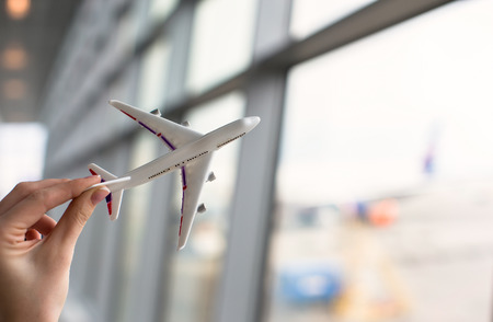 Close up hand holding an airplane model background the airport Stock Photo