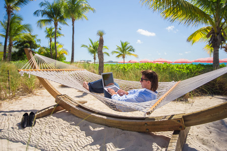 Young man using laptop on the beach Stock Photo
