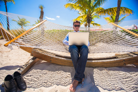Young man using laptop on the beach photo