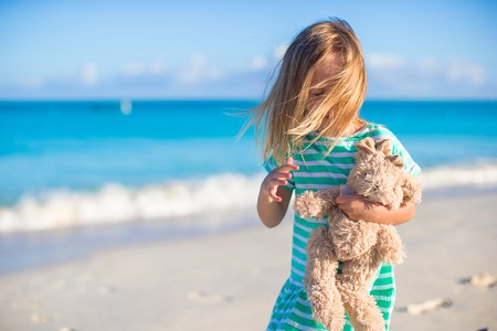 Adorable little girl with her toy on tropical beach vacation photo