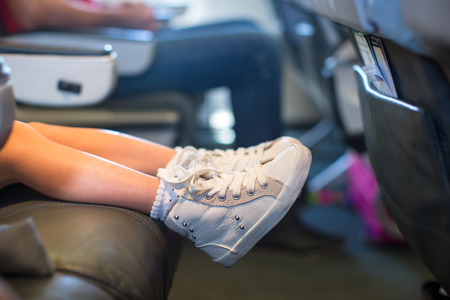 Baby feet on the seat in the plane Stock Photo