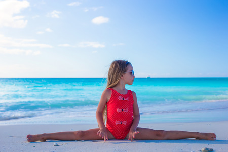 Little girl sitting on the splits at the white beach photo