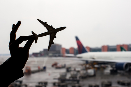Close up hand holding an airplane model background the airport photo