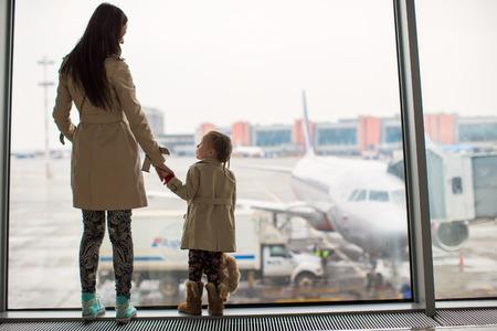 Madre y pequeña hija mirando por la ventana a la terminal del aeropuerto