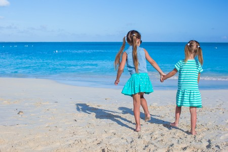 Back view of two sisters looking at the sea on the white beach Stock Photo - 28092307