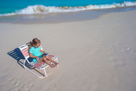 girl with laptop: Little adorable girl with laptop on the beach