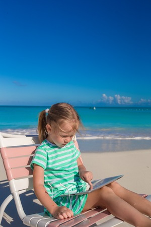Little adorable girl with laptop on the beach photo