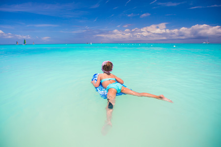 Little cute girl swimming on a surfboard in the turquoise sea photo
