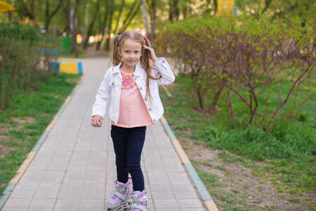 Little adorable girl on roller skates in the park in sunny day photo