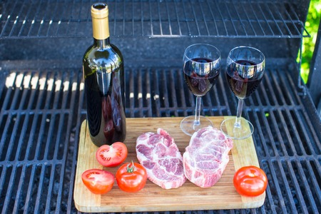 Fresh meat, vegetables and wine on a picnic outdoors photo