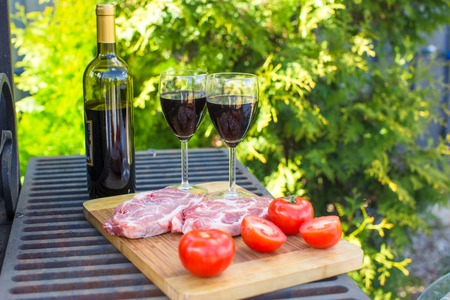Fresh meat, vegetables and wine on a picnic outdoors