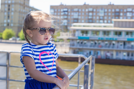 Little girl on the deck of a ship sailing in the big city photo