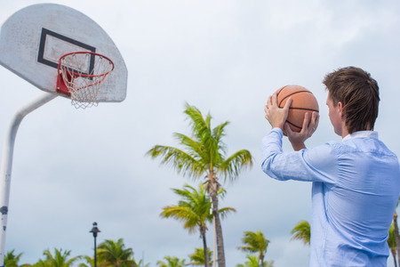 basket ball: Young man playing basketball outdoor at exotic resort Stock Photo