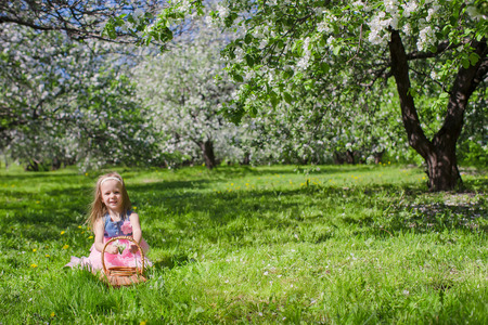 Little adorable girls with butterfly wings under blossoming apple tree