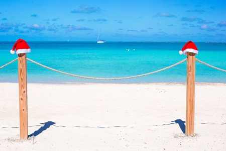 Close-up santa hat on fence on tropical white caribbean beach photo