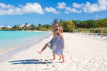 Little girls walking along the white beach and having fun Stock Photo - 28409824