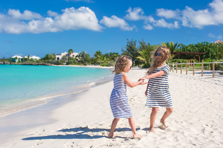 Little girls walking along the white beach and having fun Stock Photo - 28409827