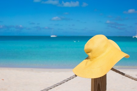 Yellow hat on the beach fence at caribbean exotic island photo