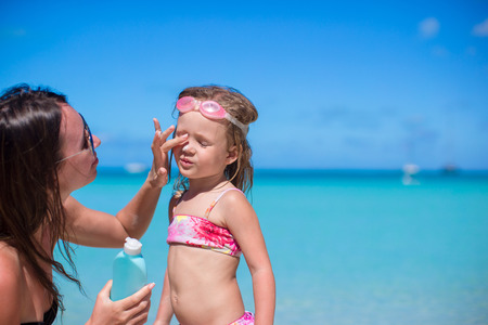 Child protection sun cream on the beach photo