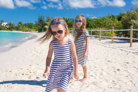 youngbaby: Little cute girls enjoy their summer vacation on beach Stock Photo