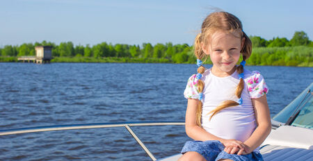Little cute girl sailing on a luxury yacht photo