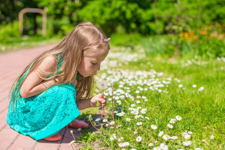 Cute little girl blowing a dandelion in summer garden photo