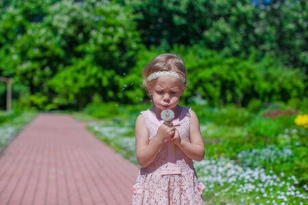 Cute little girl blowing a dandelion in summer garden photo