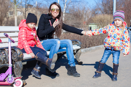 Young mother and little happy girls enjoy sunny day photo