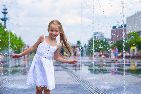 Adorable little girl playing in street fountain photo
