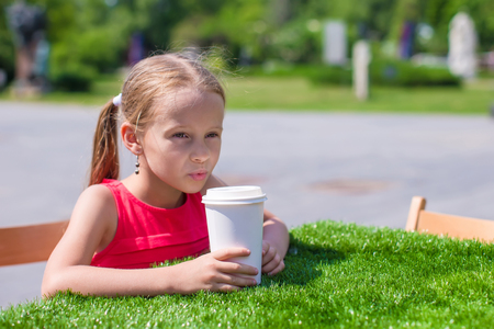 Little adorable girl at outdoor cafe on warm day photo