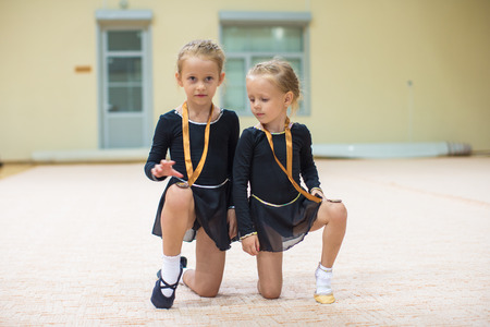 Two young gymnasts in the gym in black photo