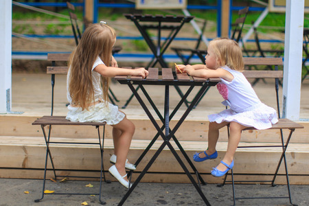 Little adorable girls at outdoor cafe on warm day photo