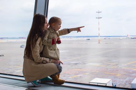 Mutter und kleine Tochter schaut aus dem Fenster auf den Flughafen-Terminal Standard-Bild - 28952318