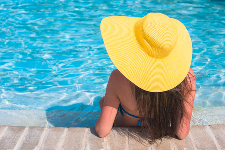 Young beautiful woman enjoying vacation in the swimming pool photo