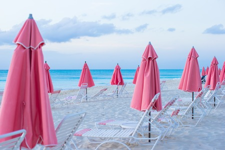 Paradise view of nice tropical empty sandy plage with umbrella and beach chair photo