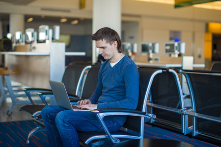 Young man with a laptop at the airport photo