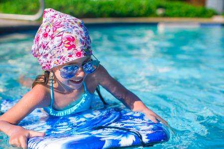 Little cute girl swimming on a surfboard in the pool photo