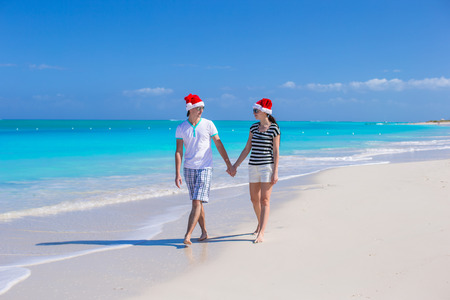 Young romantic couple in red Santa hats sitting on tropical white sand beach photo