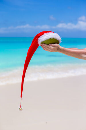 Coconut with Santa hat in male hands against the turquoise ocean photo