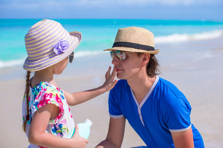 Little girl gets sun cream on her dads nose photo