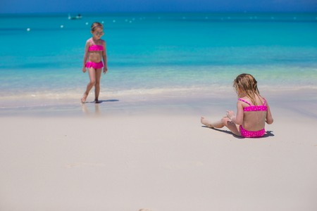 youngbaby: Little girls walking along the white beach and having fun