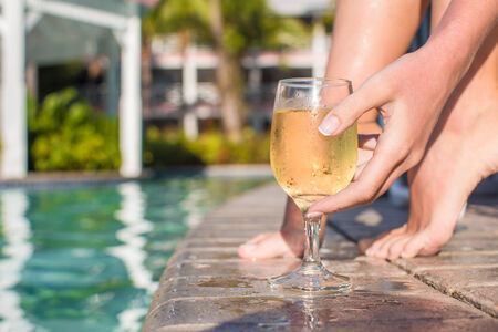 Young woman with glass of wine near the pool photo